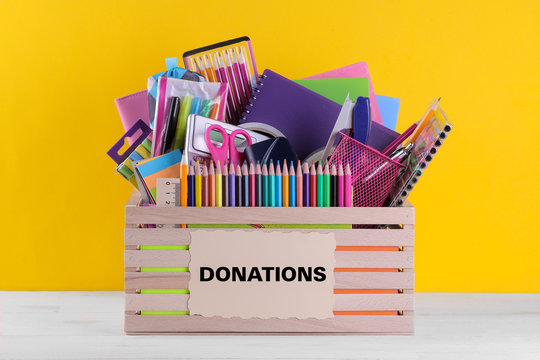 Box with various school and office supplies with a sign on a bright yellow background. Donation concept