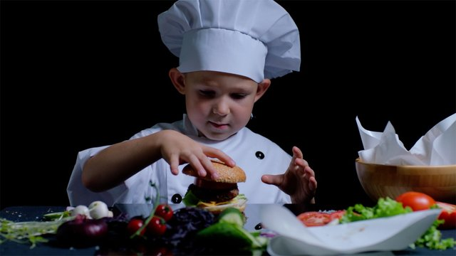 Little boy is cooking a burger at the kitchen, he is wearing chefs suit