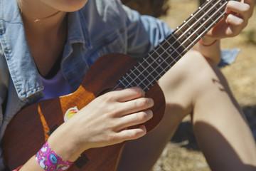 Teenager girl playing ukulele - hawaiian guitar