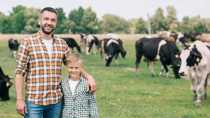 happy father and son smiling at camera while standing near grazing cattle at farm Fototapete