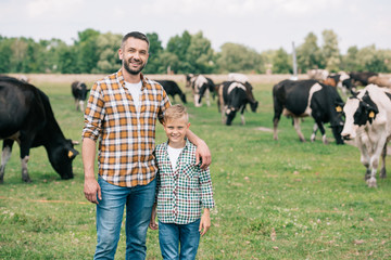 father and son smiling at camera while standing near grazing cattle at farm Wall mural