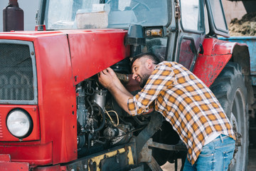 handsome middle aged farmer in checkered shirt repairing tractor Fotomurales