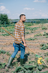farmer holding rake and watering can while walking on field