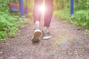 Slender female legs in plaid leggings and green sneakers go along the forest trail. Walks in the fresh air