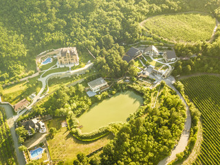 aerial top view of luxury summer cottage appartments buildings with pool near the mountain lake under dreamy sunshine