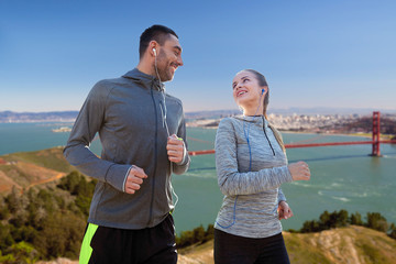 fitness, sport and technology concept - happy couple running and listening to music in earphones over golden gate bridge in san francisco bay background