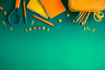 School accessories, pencils, paints, pens on green background. Back to school. Word school, wooden letters. Flat lay, top view, copy space