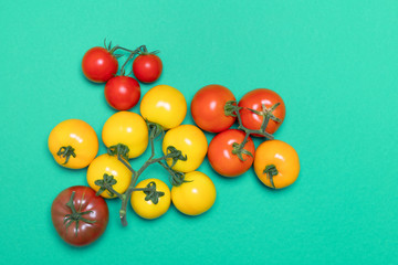 healthy and organic tomatoes of different colors on green background