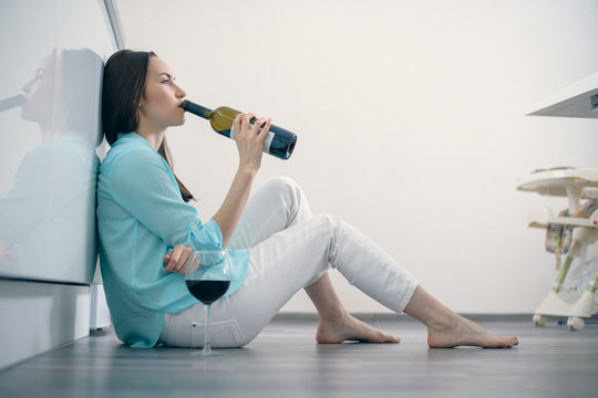 A woman in white jeans and a turquoise shirt sits on the floor in the interior of a white kitchen and drinks red wine from a bottle, divorce, alcohol, parting, grief, dependence, fatigue