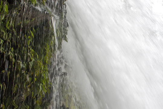 Close Up Underneath Waterfall with Dripping Green Cliffside