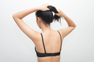 Woman tied hair and bra on white background
