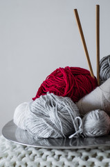 multi-colored thread for knitting in a dish. Yarn for knitting on a white background. Knitting as a kind of needlework. Knitting needles