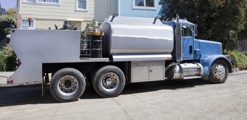 Grading and paving industrial truck parked on residential neighborhood street.
