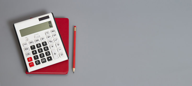 white calculator and red organizer on the grey table with red pencil