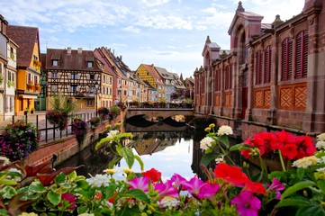Fototapete - Colorful half timbered houses along a canal with flowers and reflections, Colmar, Alsace, France
