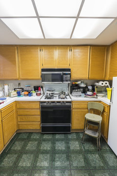 Messy condo kitchen vertical view with oak cabinets, tile countertops, gas stove, green flooring and piles of dishes.
