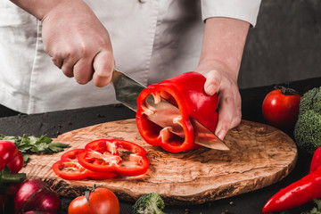 Chef cutting vegetables with knife on kitchen, cooking food. Ingredients on table. Healthy food concept. Top view.