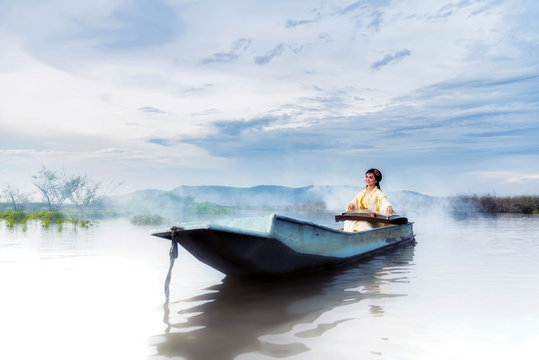 Chinese girl is playing the traditional Chinese musical instrument on the boats in the  lake ;Chinese plucked zither a traditional chinese musical