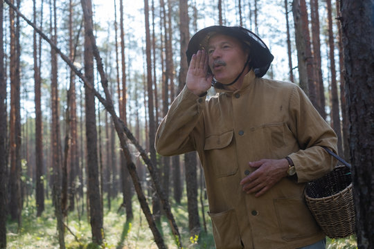 Where are you concept. Mature european man dressed in old clothes holding basket is lost in forest.