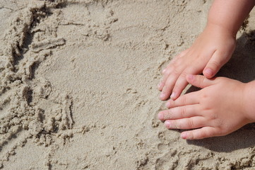 close up of kids hands, touching sand at sea for first time