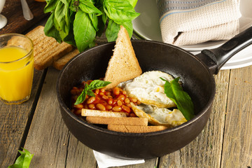 English Breakfast in cooking pan with fried eggs, sausages, bacon, beans, toasts and coffee on dark stone background
