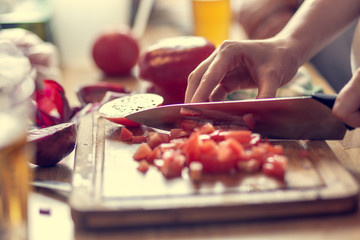 Chopping vegetables on a wooden board at home. Shallow depth of field.