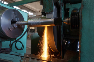 Grinding the shaft on the machine with sparks and cooling, at different angles.