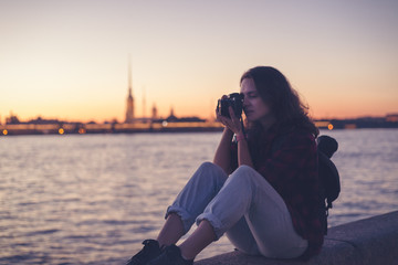 Beautiful young woman shoots on the camera views of the night city, St. Petersburg Russia