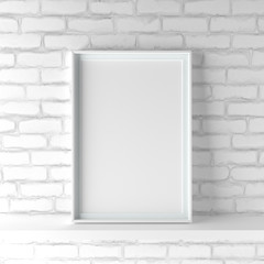 Minimalistic portrait picture frame standing on white painted brick wall