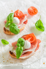 Homemade bruschetta with mozzarella, prosciutto and tomato