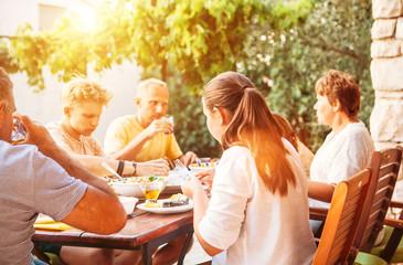 Big family have dinner on open garden terrace