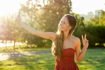 model woman long-haired in red dress does selfie on the phone rays of sun park background