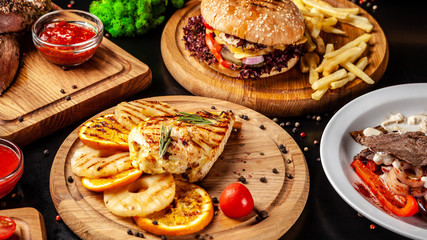 American fast food, burgers, french fries, meat and chicken steaks. Background image. set of several dishes. Copy space