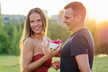 lover guy gives a gift box to embarrassed attractive beautiful blonde long hair girl in love in evening cocktail dress in summer park with grass greens background. Valentine's Day concept