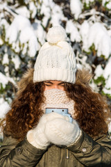 Portrait of a young beautiful lady in hipster white knitted mittens drink hot tea on a bright winter day. Close-up of a cup with hot liquid in hand. Trees in pure first snow on a background.