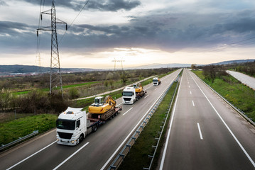 Tow Trucks in a convoy or caravan carrying Construction Machines Excavators along the Highway