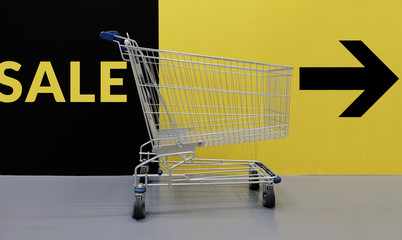 Shopping Lifestyle with Sale Promotional Concept. Empty Cart with Text and Arrow Direction on the yellow Wall , ready for Customer to Pickup or Buying Products