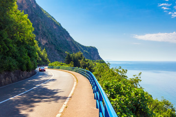 Asphalt curved road with car on the Adriatic sea coastline at Montenegro, vacations concept, nature landscape background Wall mural