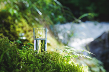 Clear water in a clear glass against a background of green moss with a mountain river in the background. Healthy food and environmentally friendly natural water Wall mural