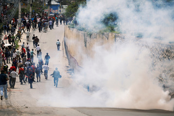 Protesters run away from a tear gas sell during the protest organized by the Sister organizations of Nepali Congress Party the main opposition party to the government in Kathmandu