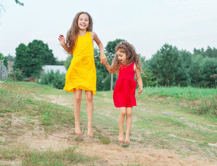 Two beautiful little girls is  jumping  at sunny summer day. Happy kids concept