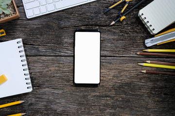 Smartphone white screen on wooden table and office supplies with keyboard, Top view with copy space.