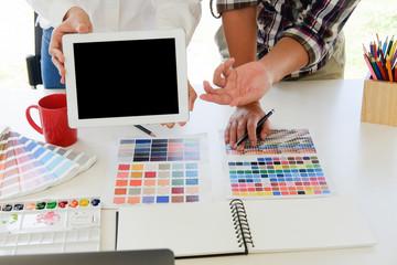 Graphic designer present something in digital tablet on artist workplace.