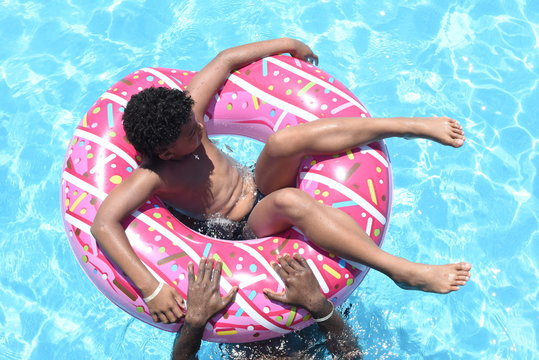 Happy cute little african-american boy lying on an inflatable donut circle  in the swimming pool in the hotel. Cool summer holidays for children and kids. Active games on the water.  Pink donat.