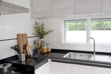 Modern white kitchen unit with built-in electric appliances and cooking stove.