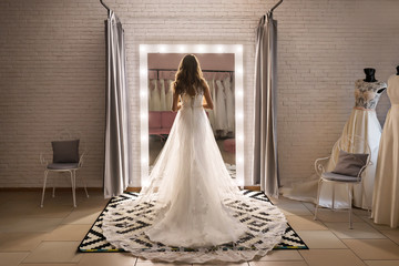 beautiful woman in wedding shop in elegant dress stands back near large mirror