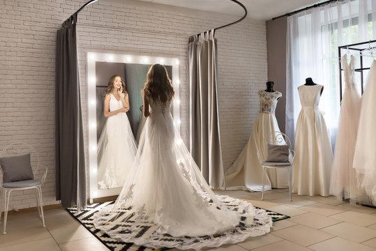 Gorgeous woman  in wedding salon is wearing a dress near loft mirror