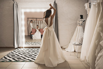 beautiful woman in wedding shop trying on a dress back