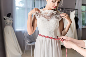 Seamstress helping bride in wedding salon. Measuring waist by centimeter