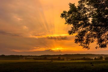 Goldene Sonnenstrahlen durchbrechen die Wolken an einem sommerlichen Tag an der Ostsee